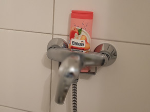 Almost invisible shower gel bottle holder