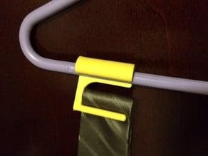 Clip-on neck tie holder for coat hanger