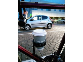 Bike cupholder for takeaway coffee. Affixes to frame on bottle cage mounts.